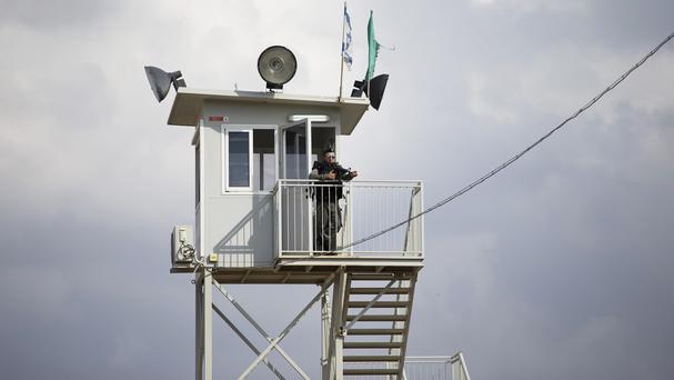 An Israeli border police officer watches from a tower at a checkpoint near the West Bank town of Nablus (AP)