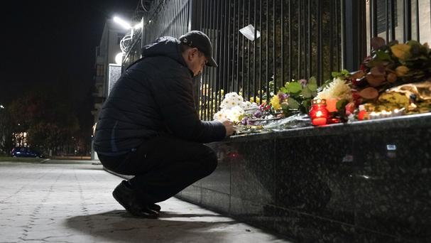 A man lights a candle to pay tribute to victims of the Russian plane crash at the Russian Embassy in Kiev (AP)