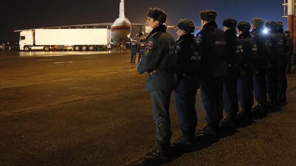 Russian Ministry for Emergency Situations employees stand preparing to load the bodies of the victims from the ministry's plane in St Petersburg (AP)