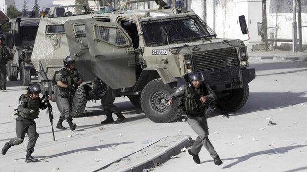 Israeli border police run during clashes with Palestinian students in Abu Dis, West Bank (AP)