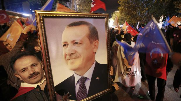A supporter of the Justice and Development party (AKP) holds a portrait of Turkey's President Recep Tayyip Erdogan after his election victory (AP)