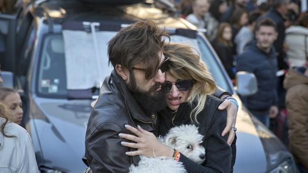 A woman cries as her partner comforts her outside the Colectiv nightclub, during a mourning march joined by thousands in Bucharest (AP)