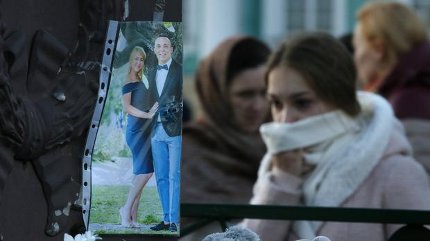 People stand next to a picture of plane crash victims attached to the fence at Dvortsovaya Square in St.Petersburg (AP)