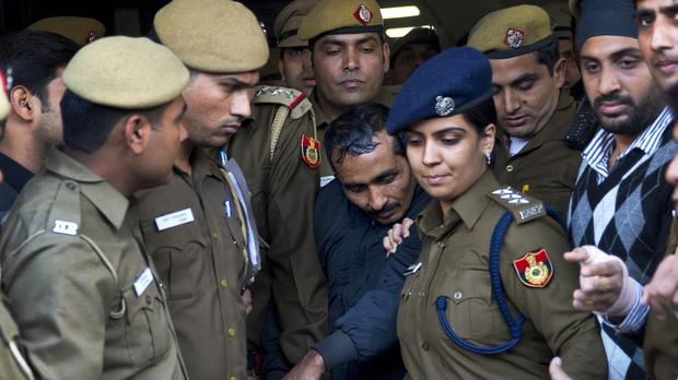 Shiv Kumar Yadav is surrounded by police as he leaves a court in New Delhi (AP)