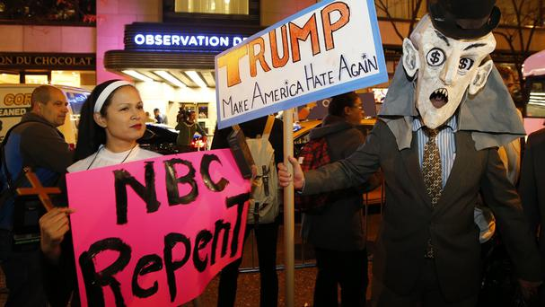 Protesters opposed to Donald Trump guest-hosting Saturday Night Live demonstrate in front of NBC Studios in New York (AP)