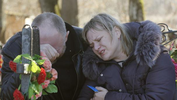 Nina Lushchenko's nephew Pavel and daughter Veronika react at her grave, after her funeral at a cemetery in the village of Sitnya (AP)