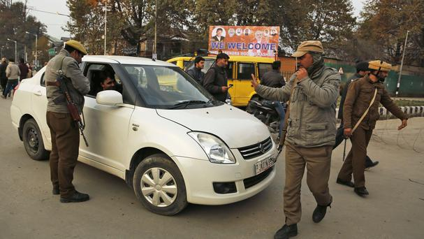 Policemen stop civilians near the venue of Narendra Modi's rally in Srinagar (AP)