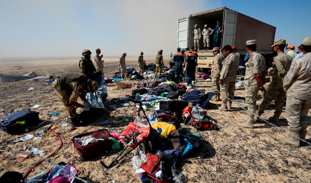 All that remains: Egyptian soldiers collect the personal belongings of plane crash victims from the impact site in the desert. Photo: Russian Ministry for Emergency Situations, via AP