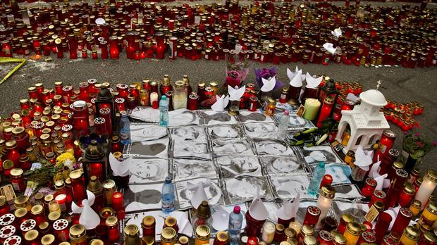 Photographs of victims are surrounded by candles in a tribute outside the Colectiv nightclub in Bucharest (AP)