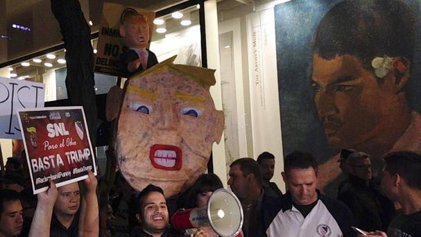 Demonstrators protest over Donald Trump's views on immigration hours before he hosts Saturday Night Live in New York (AP)
