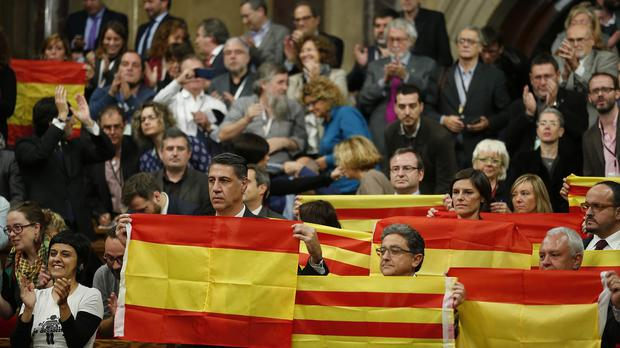 Popular Party of Catalonia members show Spanish flags and Catalonia flags at the end of a parliamentary session in Barcelona, Spain (AP)