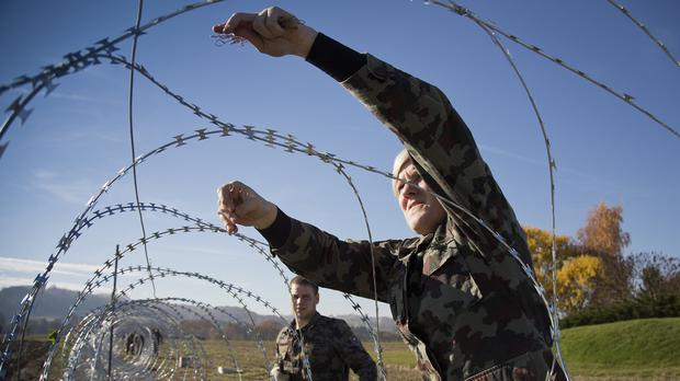A Slovenian soldier helps erect a razor-wired fence on the Croatian border in Gibina (AP)
