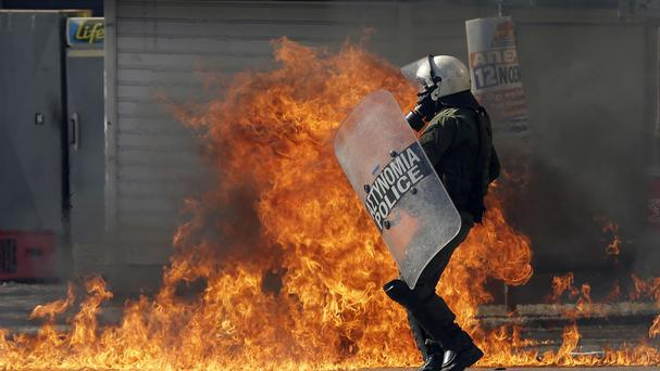 A riot policeman tries to avoid a petrol bomb thrown by protesters during a rally in Athens (AP)