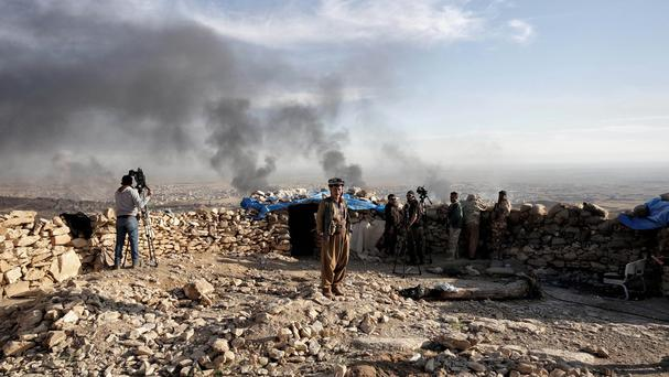 Smoke rises over Sinjar in northern Iraq from oil fires set by Islamic State militants as Kurdish fighters, backed by US-led air trikes, launch a major assault (AP)
