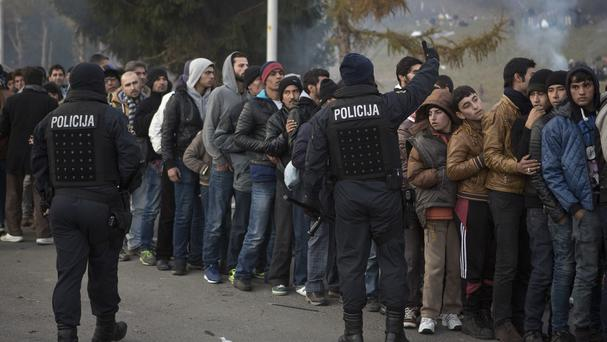 Migrants wait for food and water distribution as they wait to be allowed to cross into Austria, in Sentilj, Slovenia (AP)