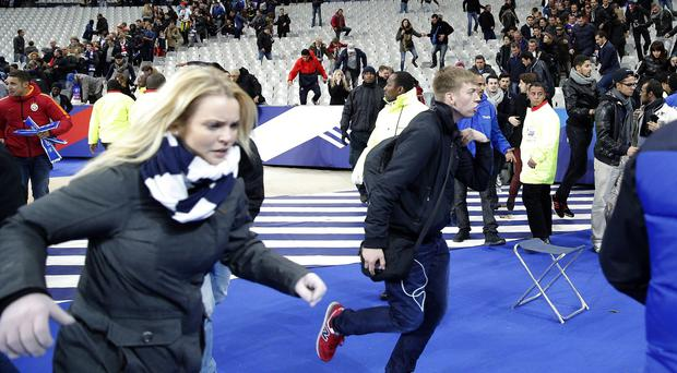 Spectators invade the pitch of the Stade de France stadium after the friendly match between France and Germany in Saint Denis, outside Paris (AP)