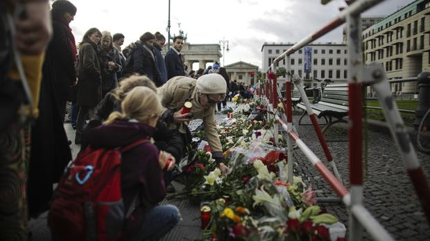 People lay down flowers for the victims killed in Friday's attacks in Paris in front of the French embassy near the Brandenburg Gate in Berlin (AP)