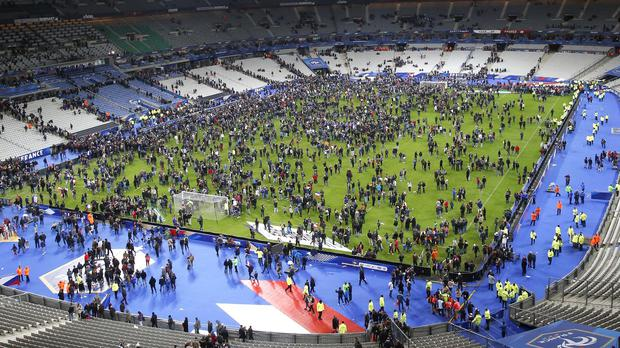 Spectators on the pitch of the Stade de France stadium after the terror alert (AP)
