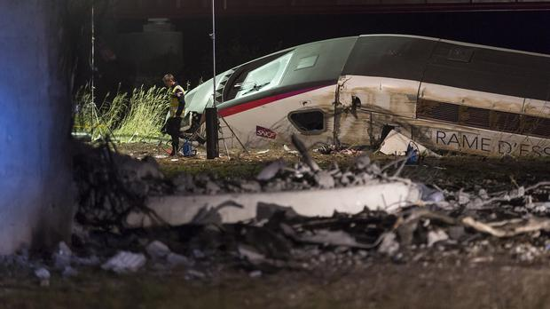 A rescue worker stands near a high-speed train which derailed in Eckwersheim, near Strasbourg, eastern France (AP)