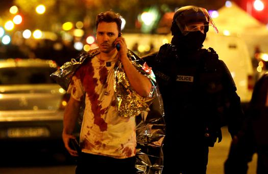 A policeman assists a blood-covered victim near the Bataclan concert hall, where terrorists took hundreds of concert-goers hostage and then began executing them.