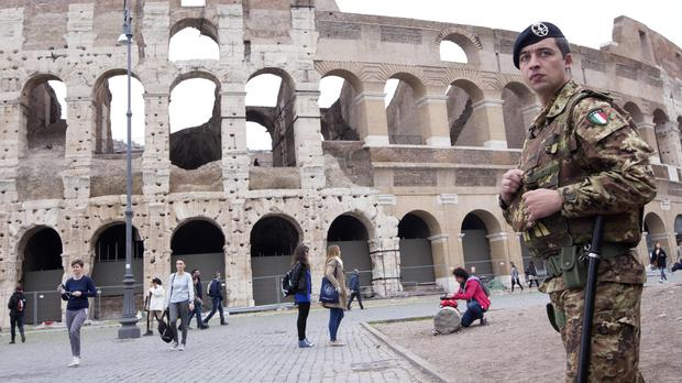 An Italian soldier patrols in front of the Colosseum in Rome (AP)