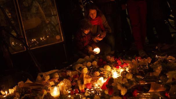 A mother and her son light candles while paying their respects in front of The Belle Equipe restaurant in Paris (AP)