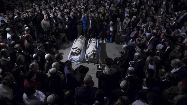 Relatives and family gather around the bodies of Rabbi Yaakov Litman and his son Netanel who were shot dead near Hebron (AP)