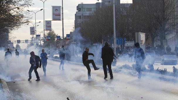 A supporter of the opposition throws back a tear gas canister at police in Kosovo capital Pristina (AP)