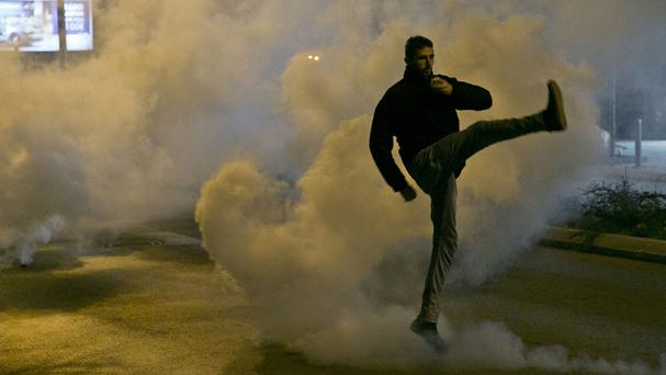 A supporter of the opposition kicks back a gas canister at Kosovo police in Pristina (AP)