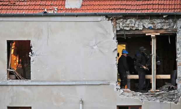 People work inside the damaged building of Wednesday's raid on an apartment in the Paris suburb of Saint-Denis