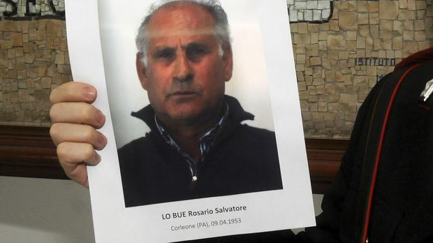 An Italian policeman holds a picture of Mafia boss Giuseppe Lo Bue during a press conference in Palermo (AP)