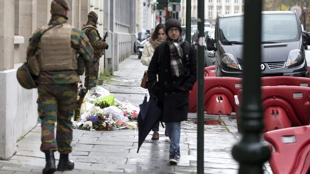Belgian army soldiers patrol next to flowers left outside the French consulates' office in Brussels (AP)