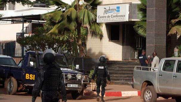 Mali police walk outside one of the entrances to the Radisson Blu hotel's conference centre after the attack by gunmen (AP)
