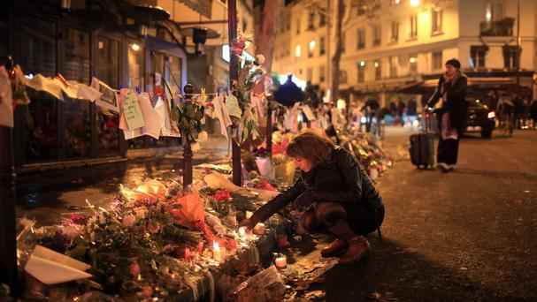 A woman lights a candle near the Cosa Nostra restaurant in Paris (AP)
