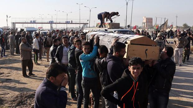 Mourners carry the coffin of a victim killed in a suicide bomb attack on al-Rida Shia mosque in the Iraqi capital's Nahiyet al-Rasheed area (AP)