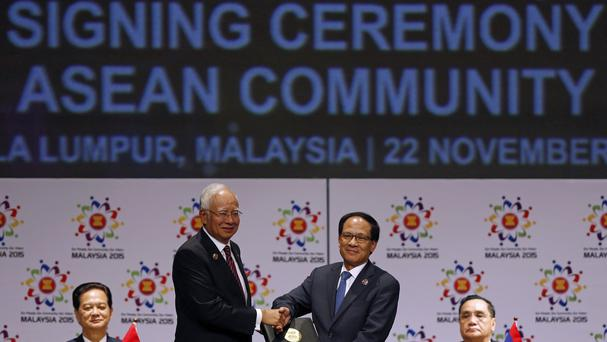 Malaysian prime minister Najib Razak, left, passes a signed document to Asean secretary general Le Luong Minh of Vietnam after the establishment of the economic community (AP)