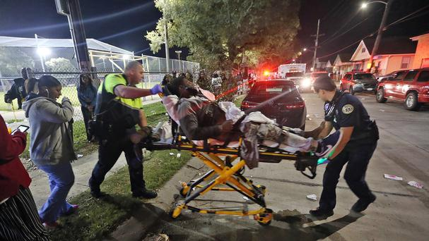 Officials remove a man from the scene following a shooting in New Orleans (Michael DeMocker/NOLA.com The Times-Picayune via AP)