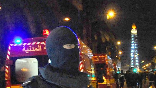 A hooded police officer prevents media from aproaching the scene of a bus explosion in the center of the capital, Tunis (AP)