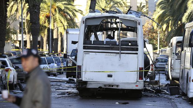 A man walks past the bus that exploded in Tunis (AP)