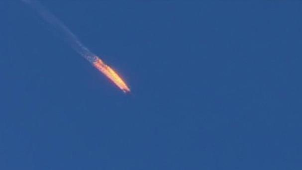 A Russian warplane on fire before crashing in Turkey after being shot down (Haberturk TV via AP)