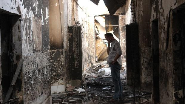 An employee of Doctors Without Borders walks inside the charred remains of their hospital after it was hit by a US air strike in Kunduz (AP)