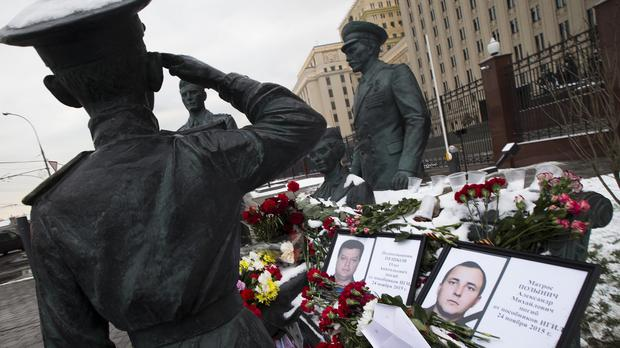 Photos of a pilot and a sailor killed in the jet incident are placed at a monument to Soviet Officers with flowers and paper jet outside Russian Army General Staff headquarters in Moscow (AP)
