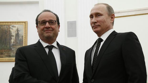 Russian president Vladimir Putin shakes hands with his French counterpart Francois Hollande during their meeting in Moscow (AP)