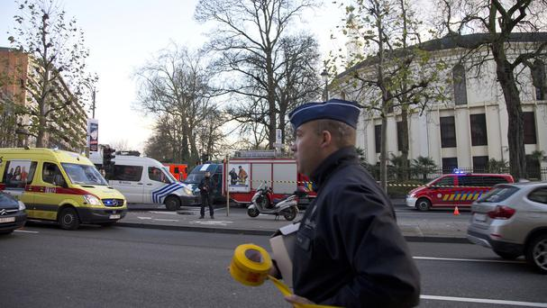 A police officer rolls out a security tape as emergency personnel respond outside the Grand Mosque of Brussels (AP)