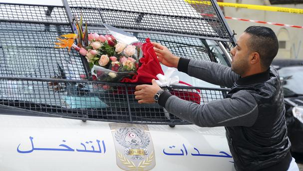 A man places a bouquet of flowers on a police van, near the bus that exploded in Tunis on Tuesday (AP)