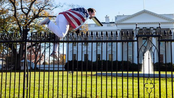 A man with a US flag wrapped around him jumps the fence at the White House (AP)