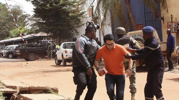 Mali soldiers help a hostage to leave the Radisson Blu hotel after gunmen attacked the hotel in Bamako (AP)