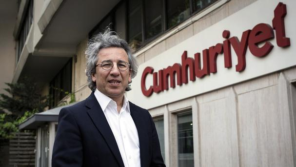 Can Dundar, editor-in-chief of opposition newspaper Cumhuriyet, speaks to the media outside the headquarters of his paper in Istanbul (AP)
