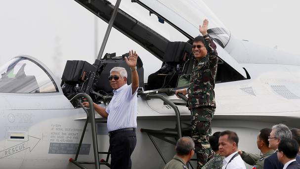 Philippine defence secretary Voltaire Gazmin, left, and armed forces chief General Hernando Iriberri wave from a newly-acquired FA-50 fighter jet (AP)