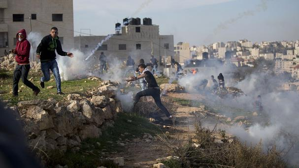 Palestinian protesters run from tear gas fired by Israeli troops during clashes near Ramallah, part of a two-month wave of violence (AP)